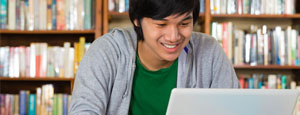 Knowledge Central mini banner - Asian American student on laptop in library.