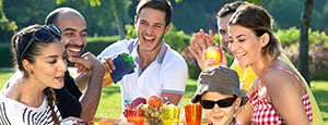 My Health mini banner - multi ethnic group of friends enjoying a meal together outdoors in the garden with a small boy